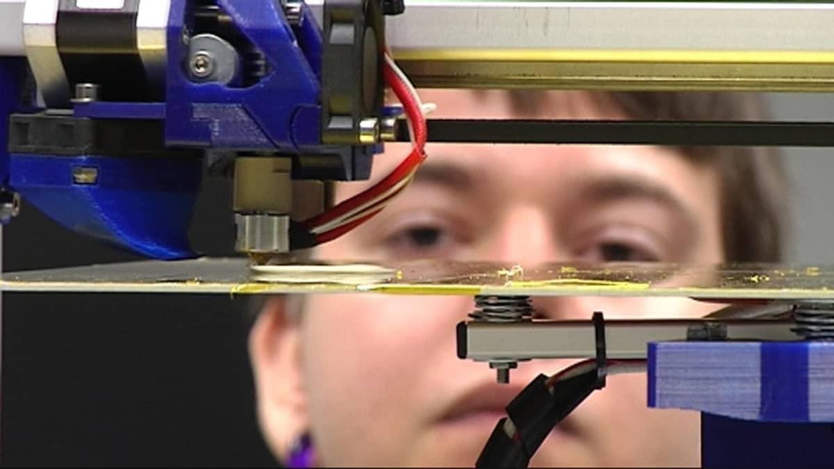 Opiskelija katsoo kun 3D-tulostin tulostaa osaa.