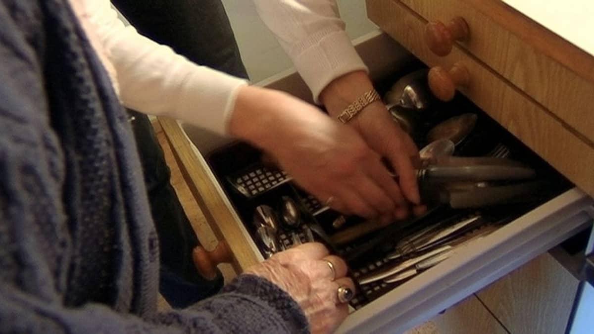 Henkilö auttamassa vanhusta keittiössä.