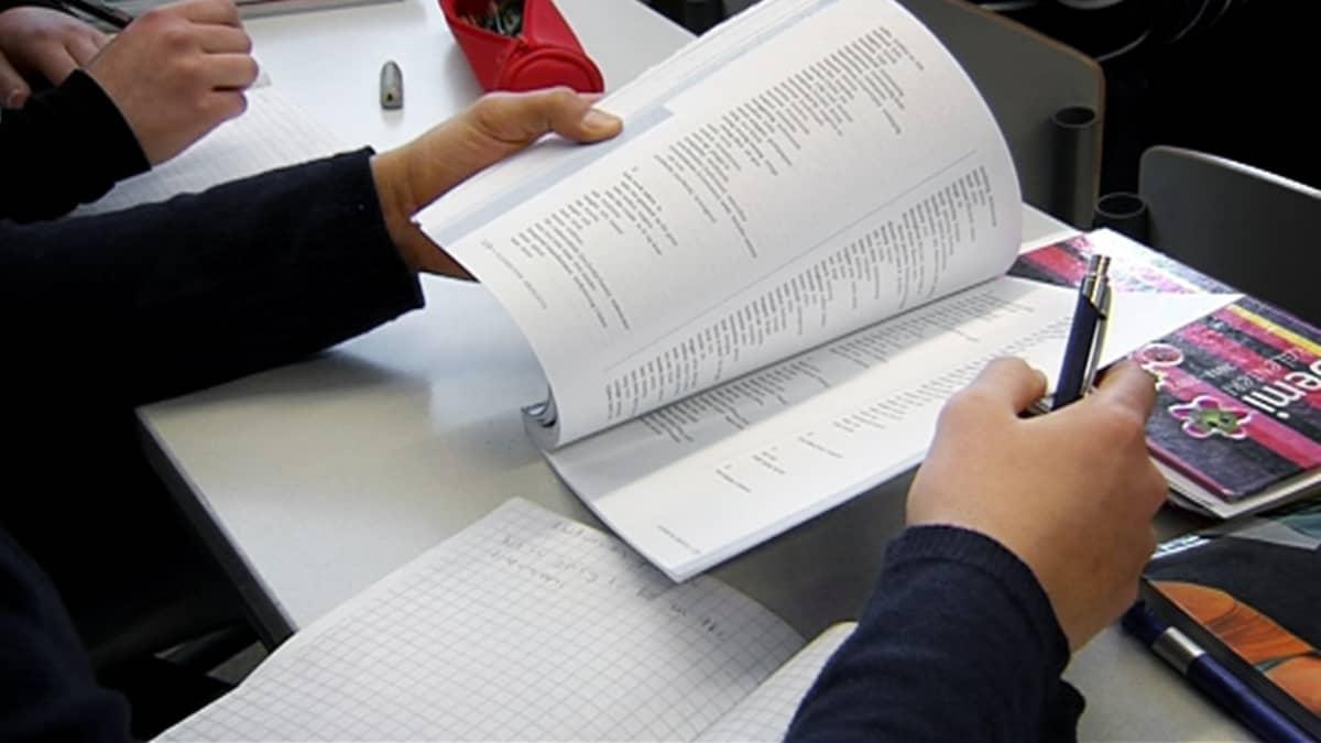 Koululainen selaa kirjaa tukiopetuksessa.