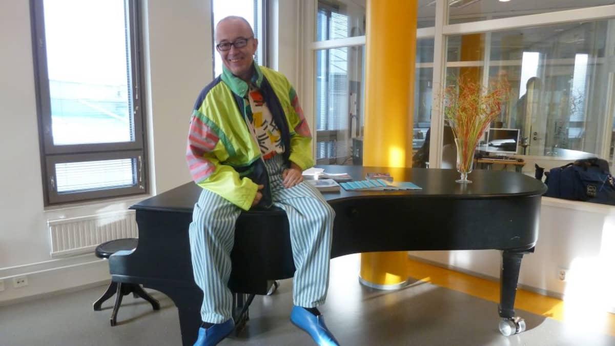 Juha Roiha istuu pianon päällä.