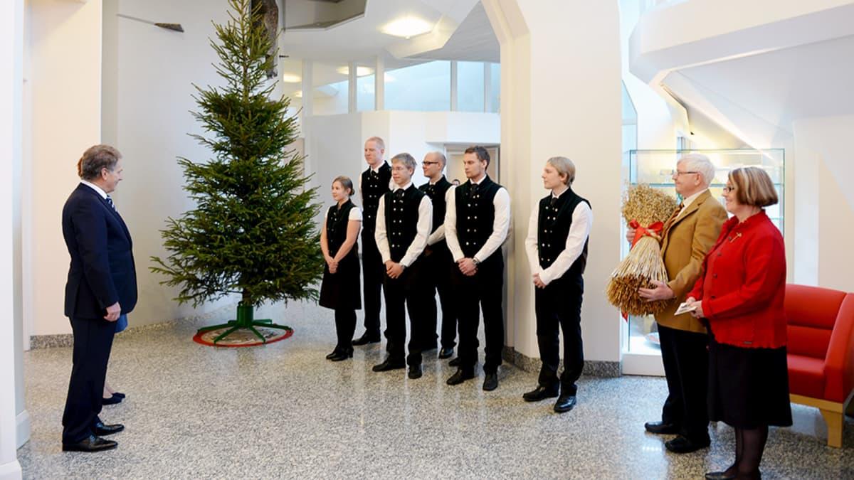 Presidenttipari vastaanottaa metsäylioppilaiden joulukuusen sekä kauralyhteen Mäntyniemessä.