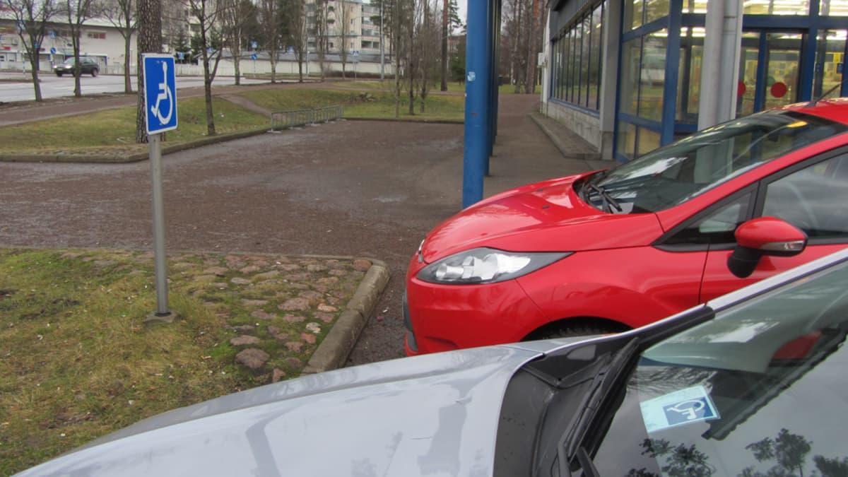 Kaksi autoa invaparkkipaikalla, toisessa pysäköintilupa toisessa ei.