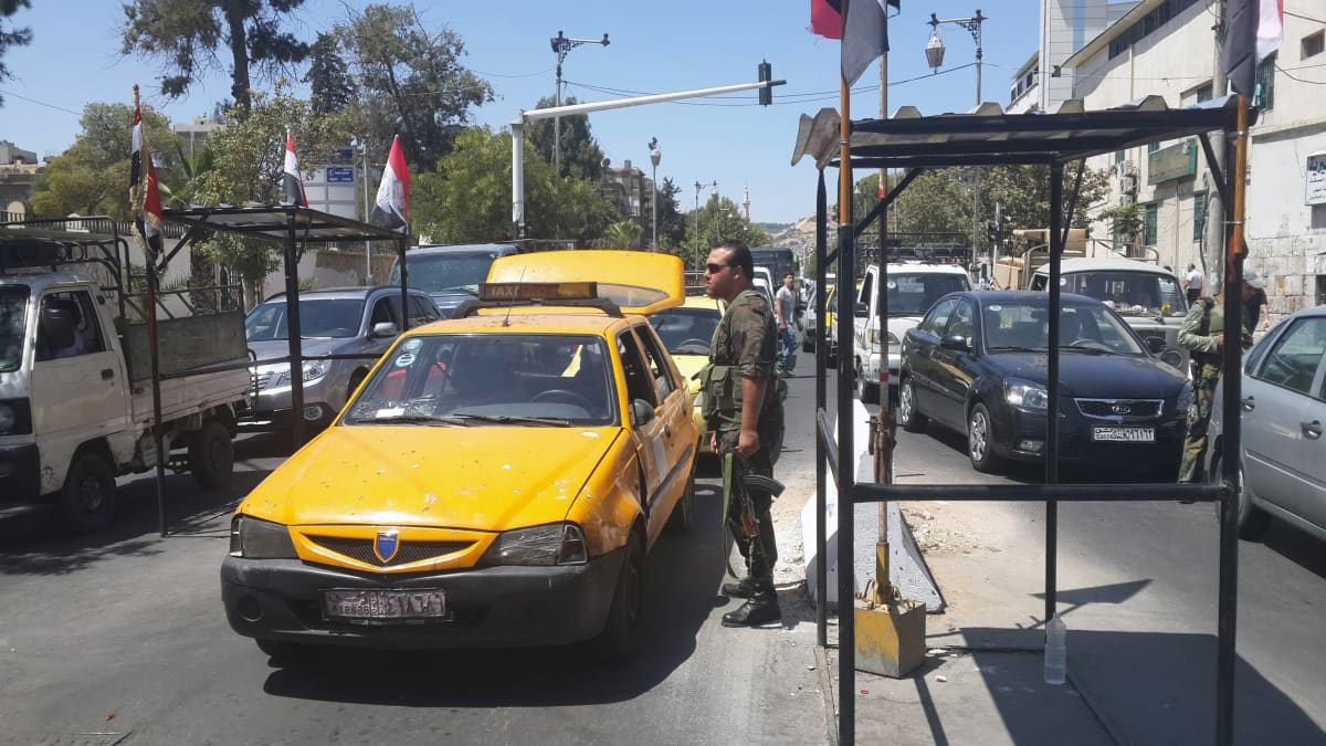 Syrian soldiers check the identities of people at a checkpoint in Baghdad Street, in Damascus, Syria, 21 August 2013