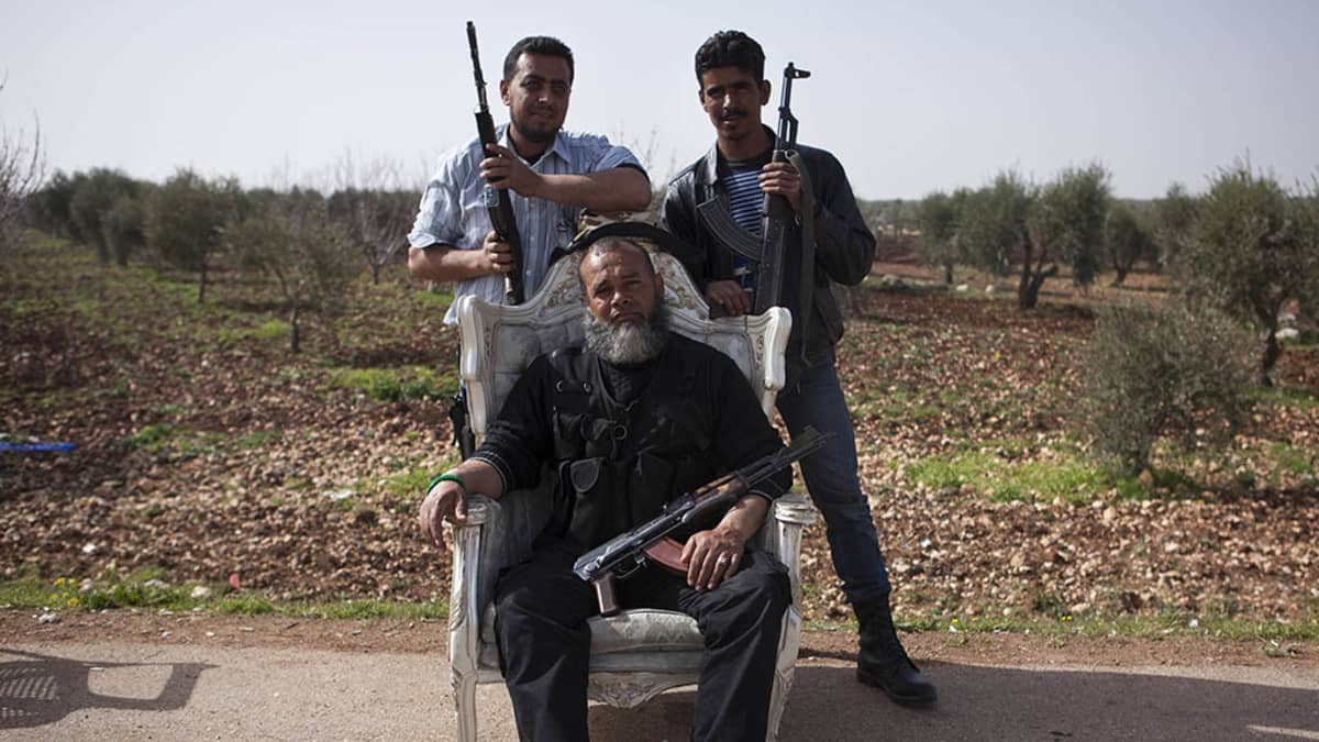 Free Syrian Army fighters hold their weapons at a checkpoint on a road to Menag Military Air Base 13 March 2013.