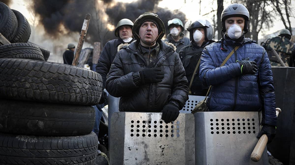 Mielenosoittajat laulavat Ukrainan kansallishymniä barrikaadeilla.