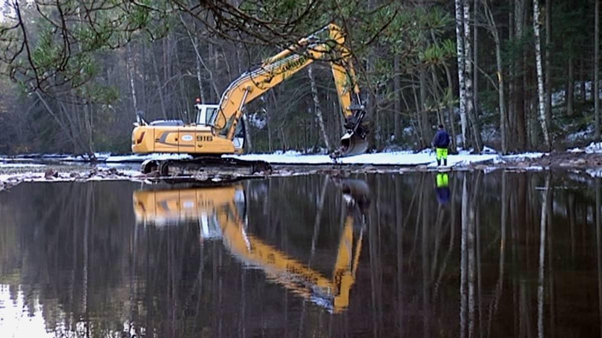 Kaivinkone rakentaa pohjapatoa jokeen.
