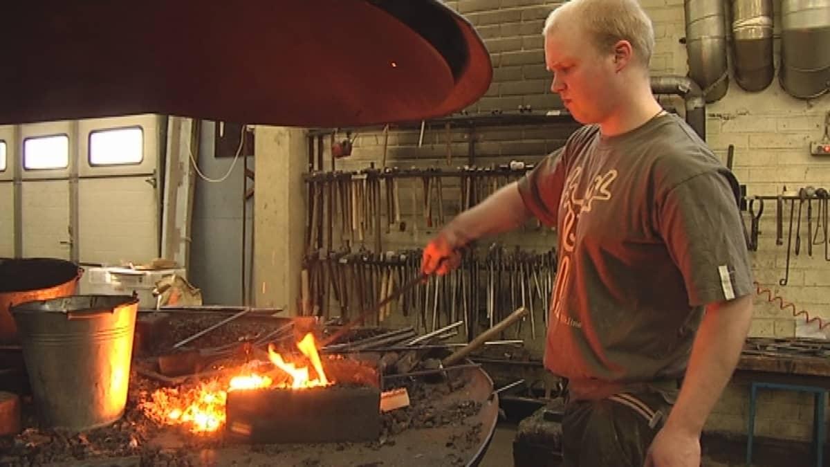 Mies lämmittää rautaa tulella.