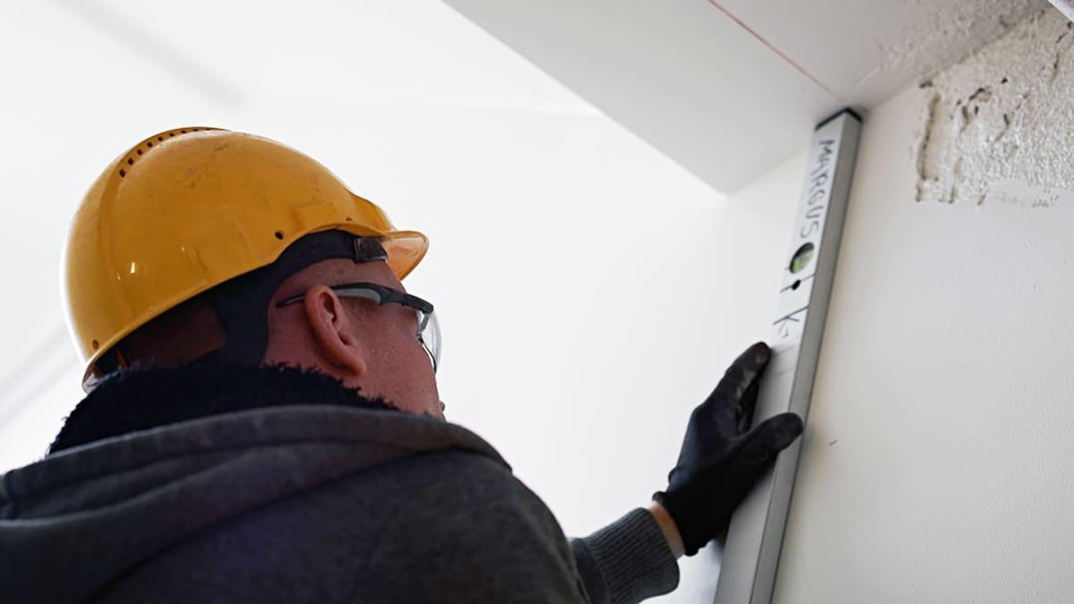 Rakennusmies mittaa seinää vesivaa'alla.
