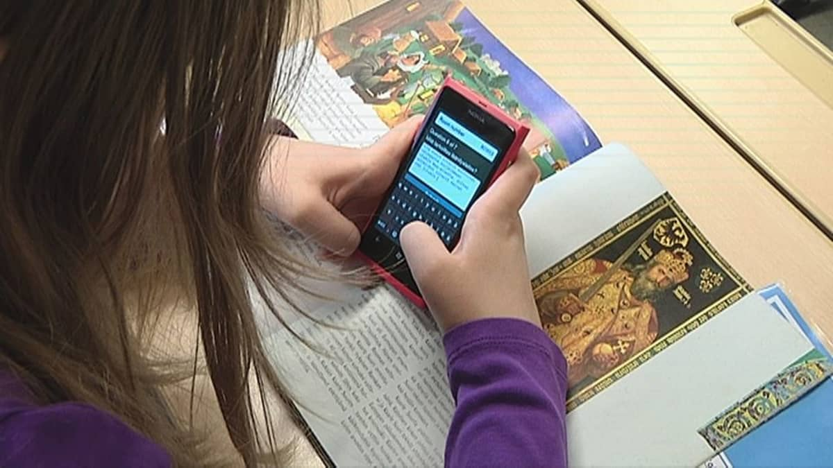 Oppilas käyttää kännykkää historiankirjan päällä.