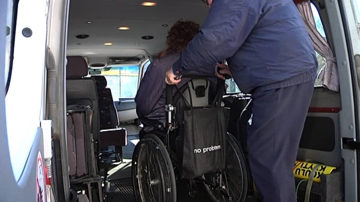Pyörätuolia laitetaan taksin kyytiin.