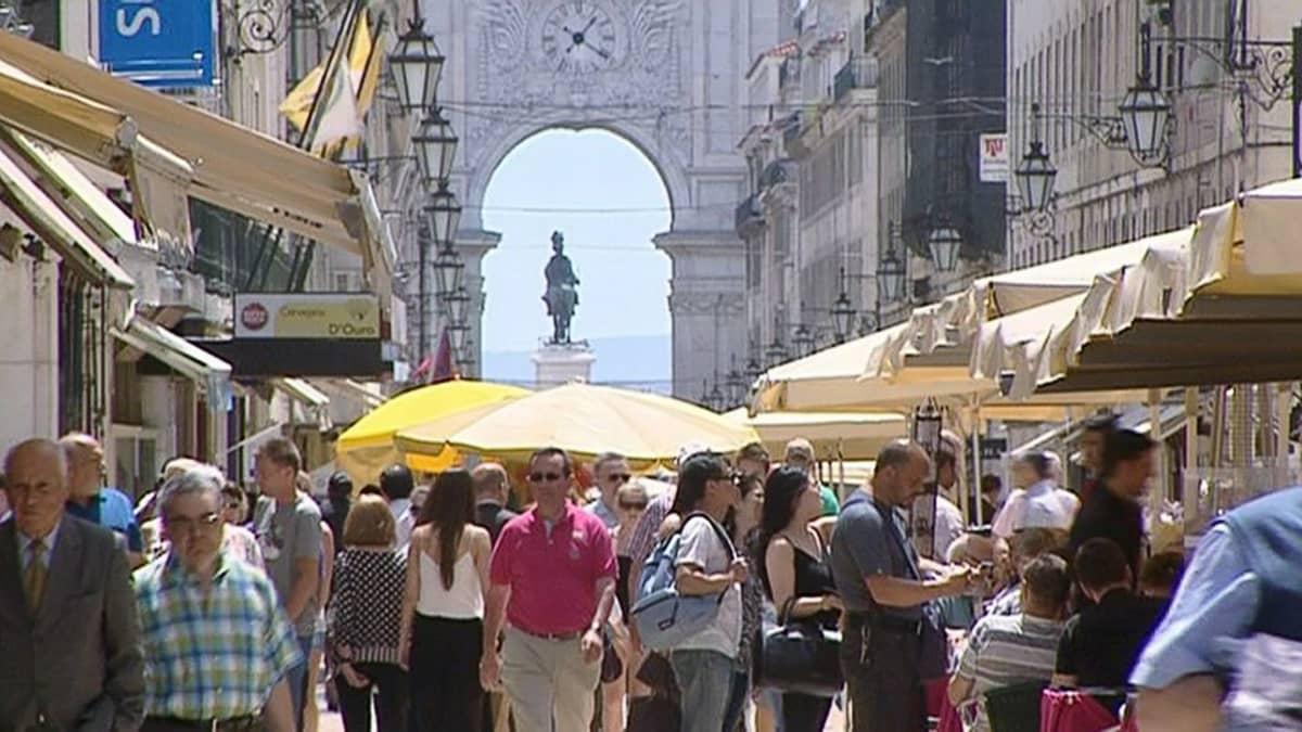 Ihmisiä kävelemässä Lissabonin keskustan kadulla.