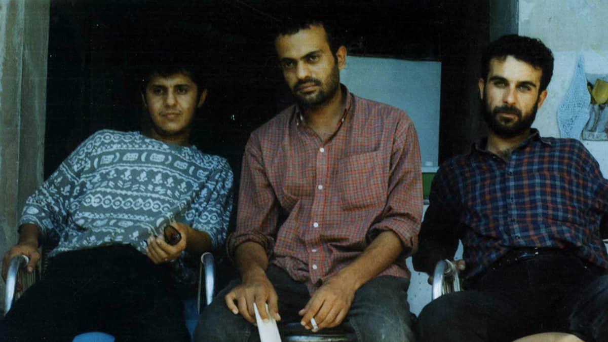 Kolme miestä istumassa.