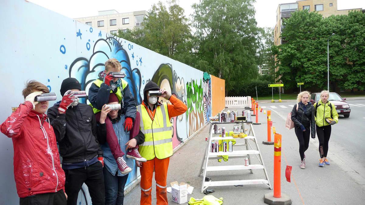 Viiden pojan ryhmä poseeraa työmaa-aitaan maalaamansa graffitin vieressä