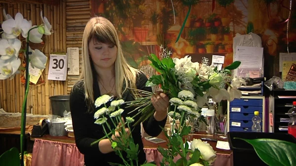 Floristi tekee kukkakimppua.
