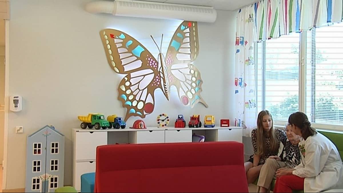 Kymenlaakson keskussairaalan lastenosaston seinää koristaa iso valaistu perhonen. Sen alla on pöytä, johon on aseteltu leluja. Oikealla vihreällä tuolilla istuu kolme henkilöä.