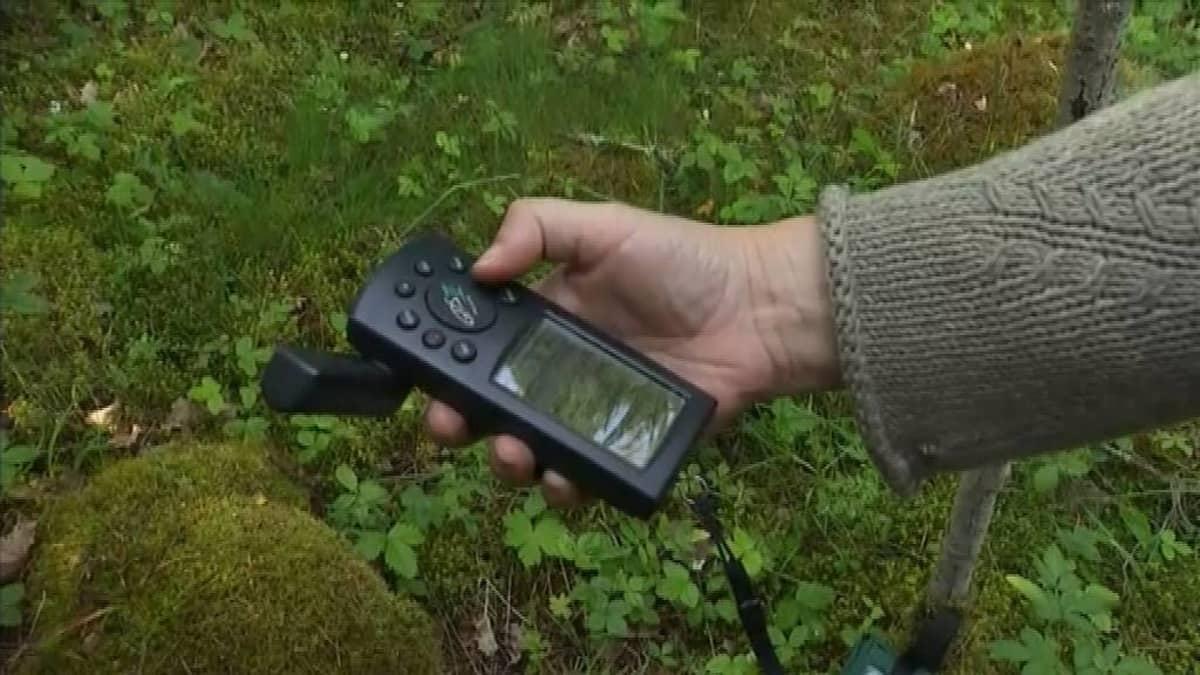 Nainen pitää kädessään GPS-laitetta.