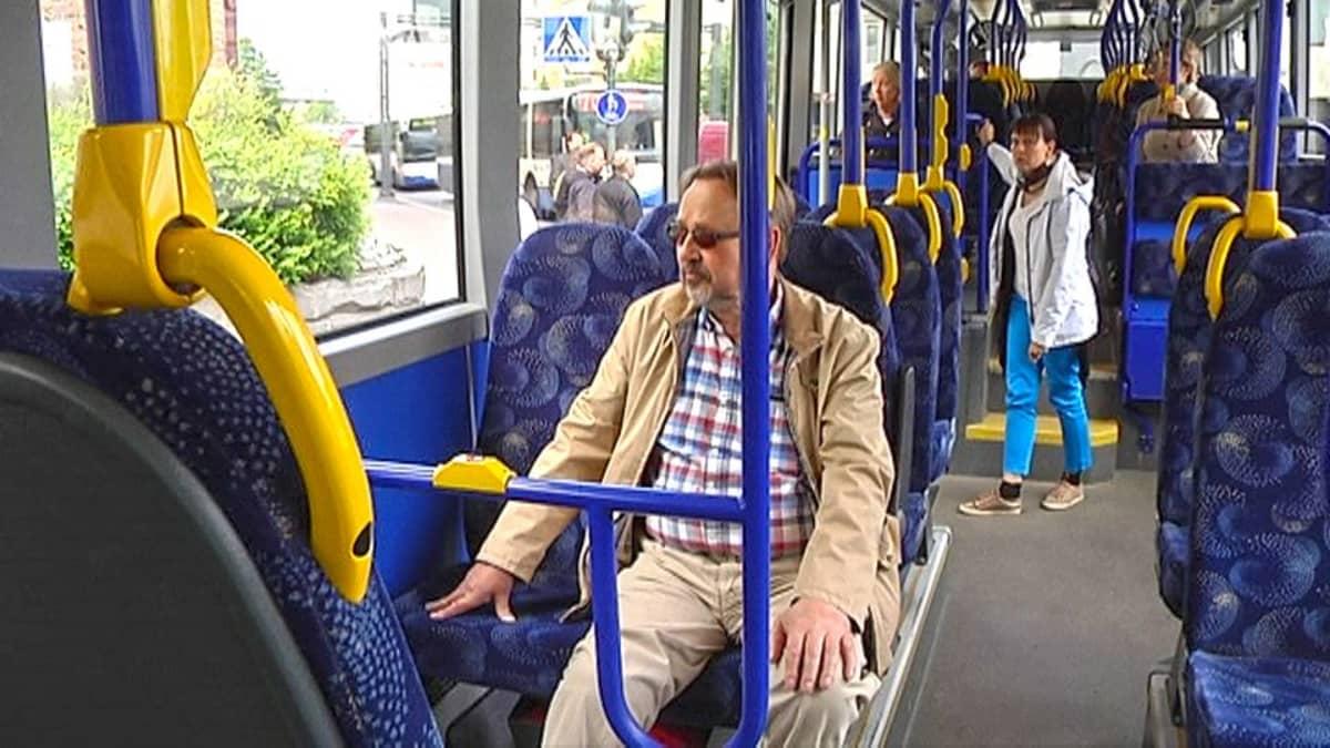 Matkustajia bussin kyydissä.