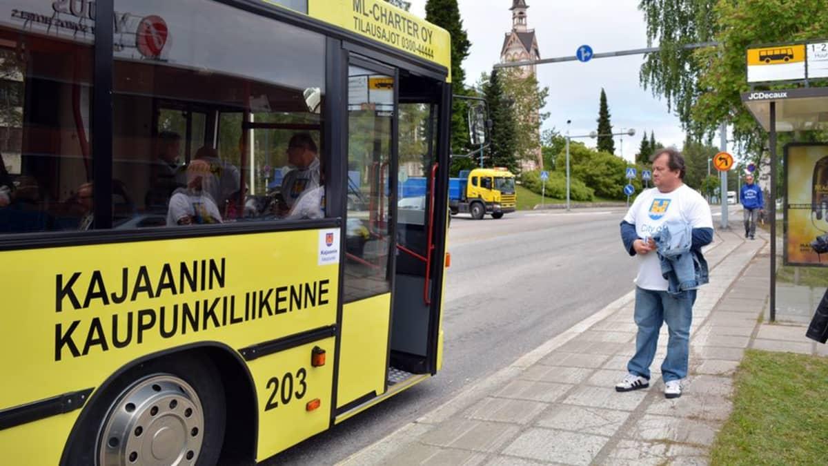 Keltainen bussi pysäkillä ja mies seisoo oven edessä.