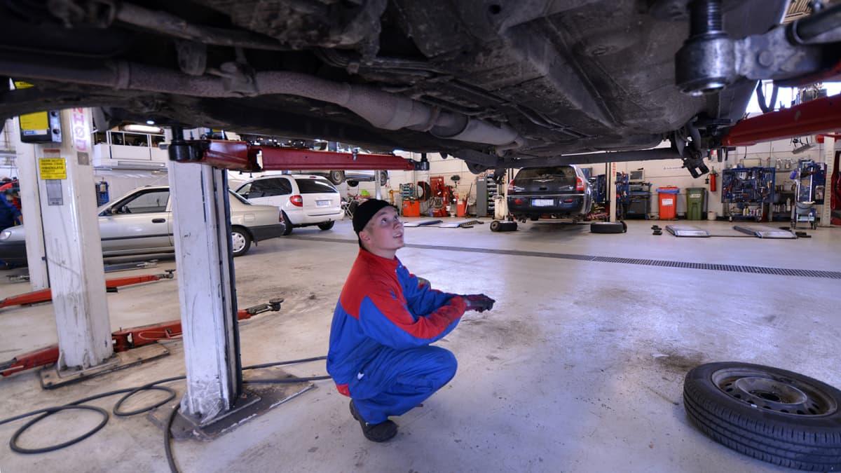 Mies tarkastaa auton pohjaa huoltamolla.