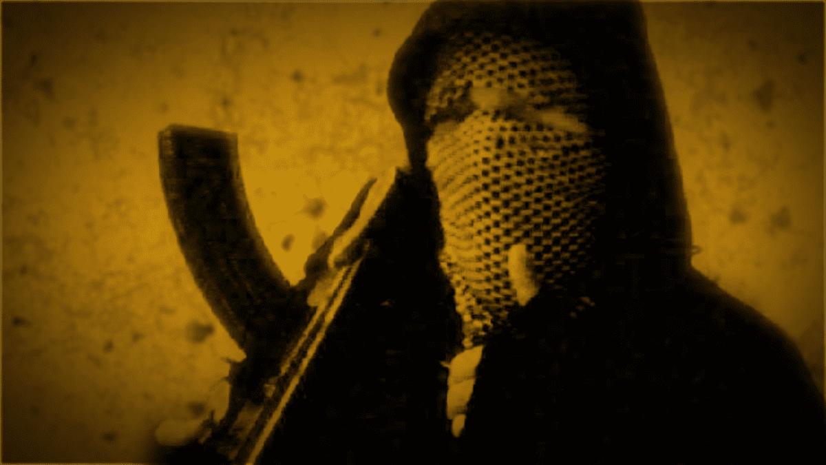 Mustaan huppuun pukeutuneella miehellä on konekivääri kädessään.