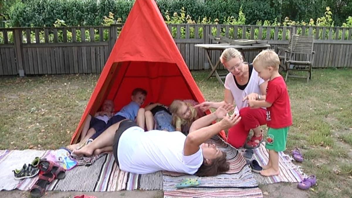 Lastenhoitaja Annukka Stolt ja lapset majan edustalla.