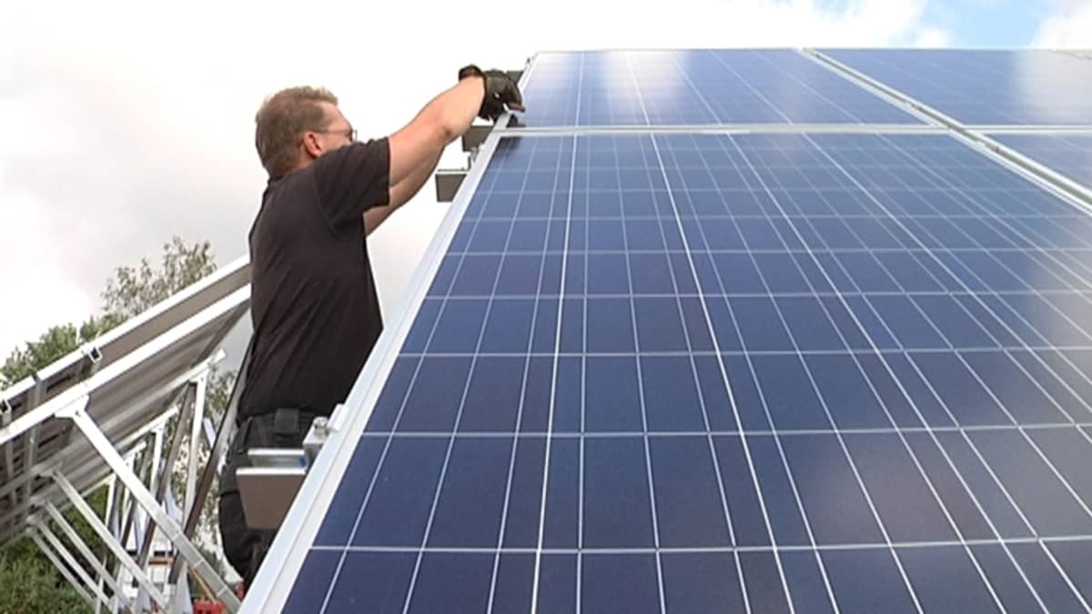 Mies tekee asennustöitä aurinkopaneelin vieressä.