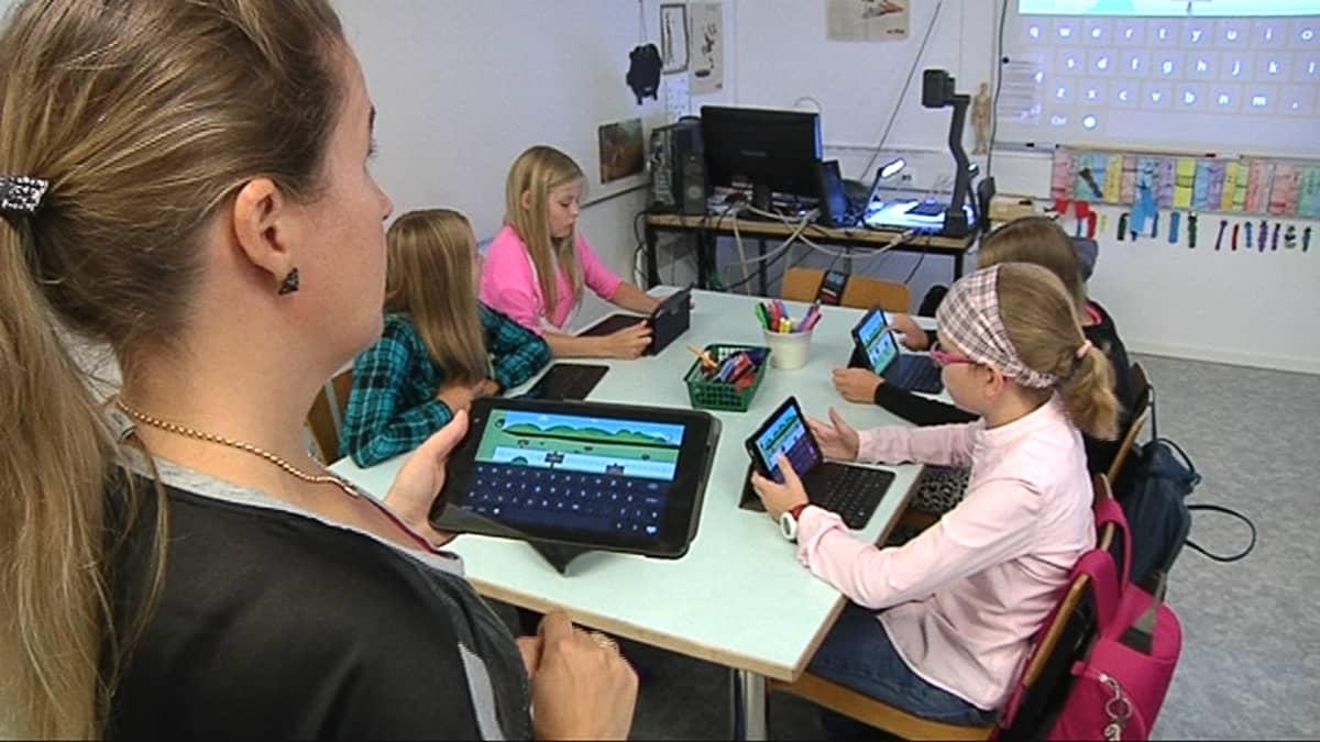 Kuvassa oppilaat ja opettaja tutkivat tabletti-tietokonetta.