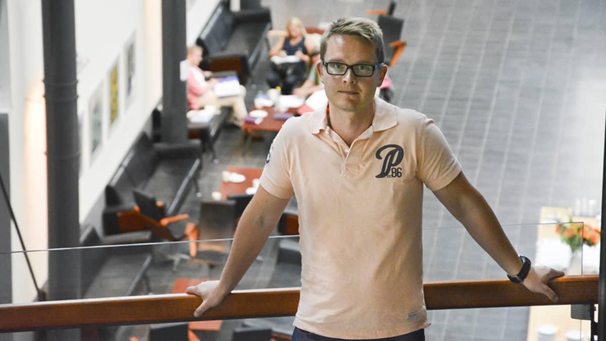 Tutkimustohtori Matti Mäntymäki nojaa yliopiston kaiteeseen.