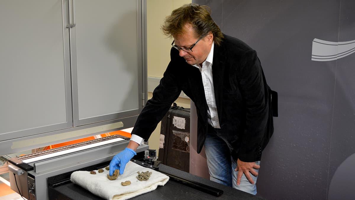 Arkeologi Jan Fast asettelee muinaisesineitä skannattavaksi Oulun yliopistossa