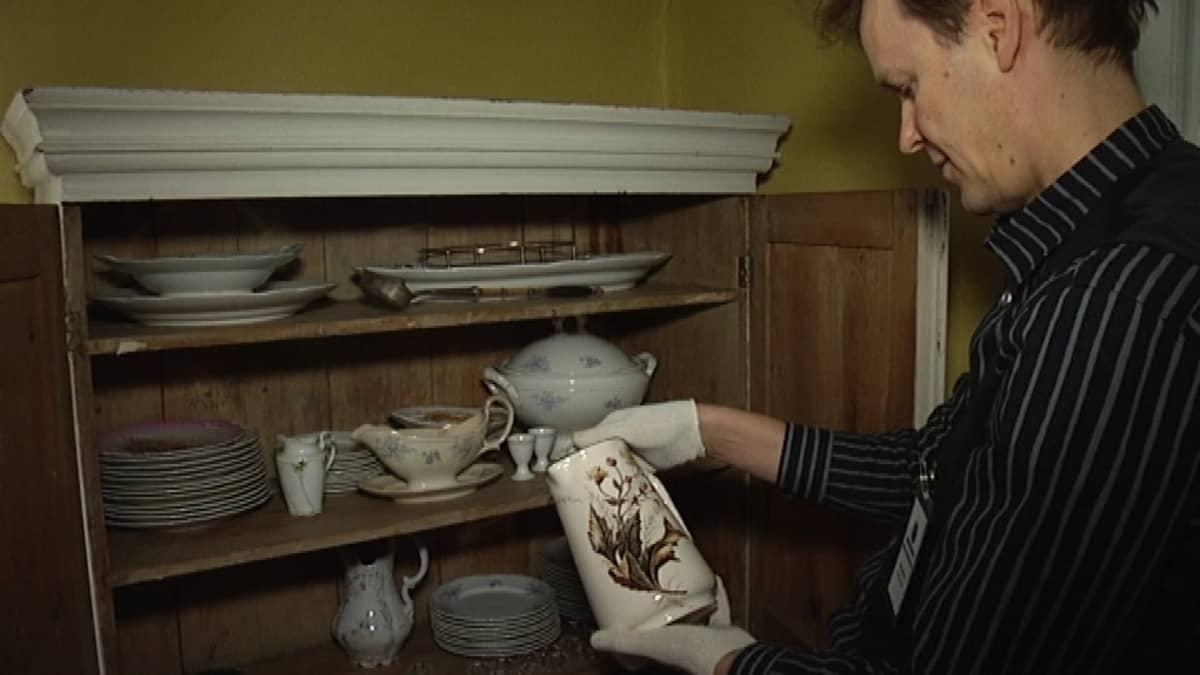 Vastaava museo-opas pitelee Urajärven kartanon astiastoon kuuluvaa kannua.