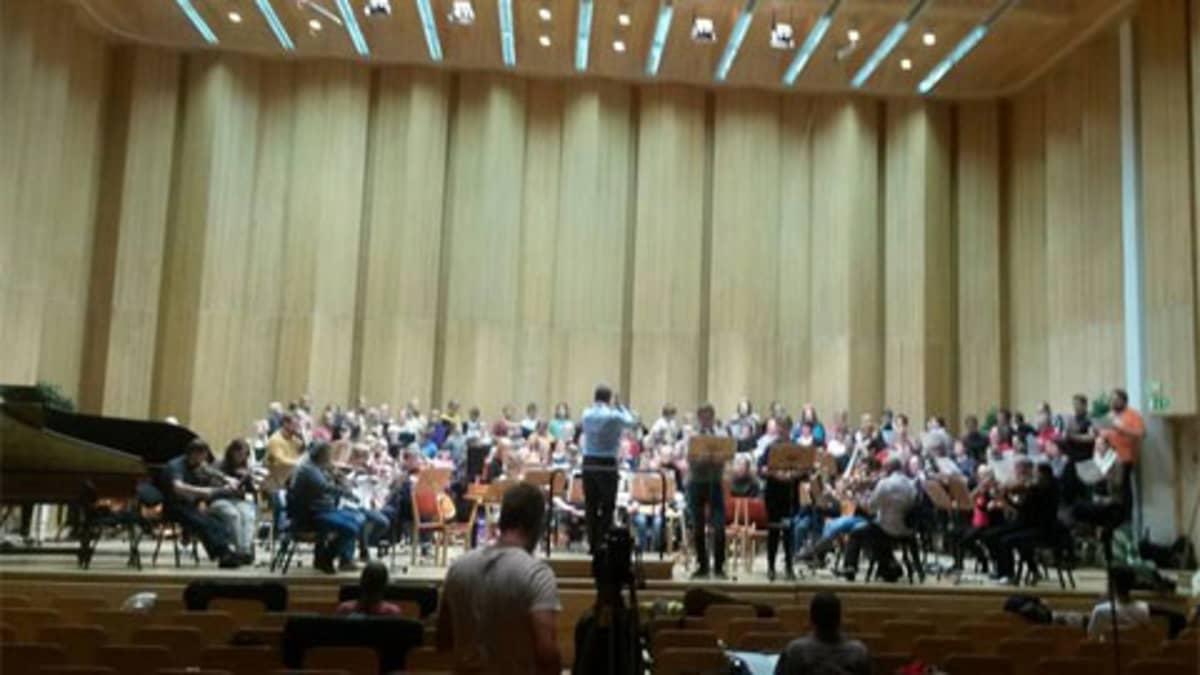 Lähes 150 esiintyjää täyttää lavan Sakari Oramon johdolla Taivaavalot-teoksessa. Kuva harjoituksista.