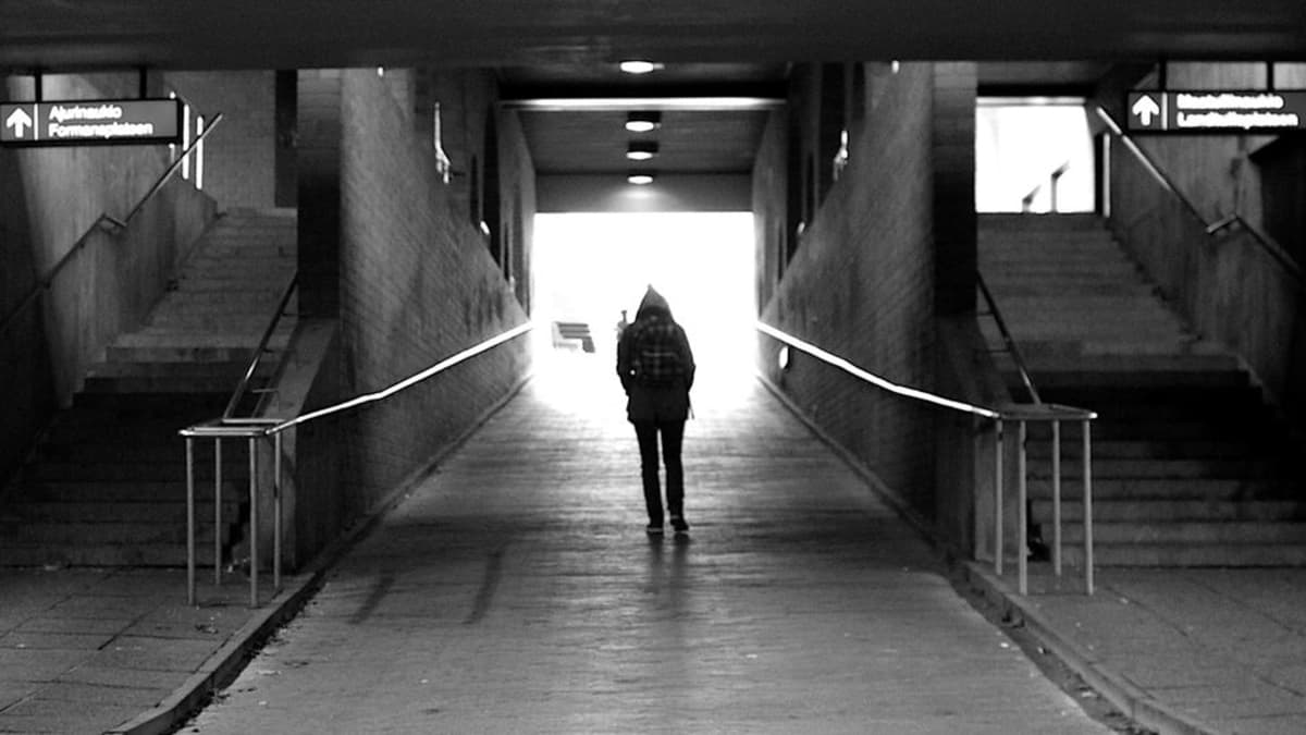 Tyttö kävelee juna-asemalla.