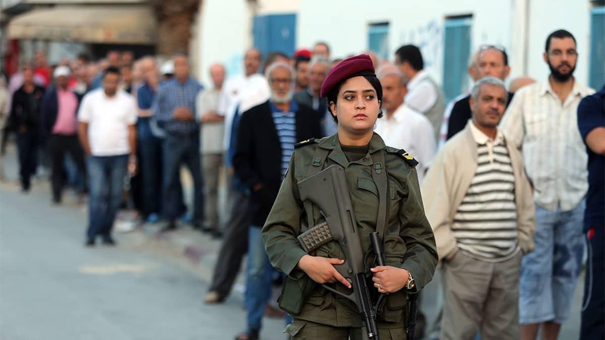 Aseistettu naisvartija ja jono miehiä hänen takanaan.
