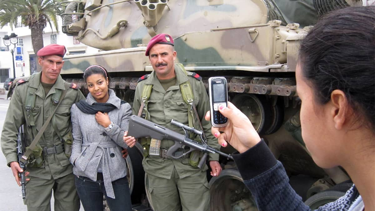 Nainen ottaa kännykällä kuvaa toisesta naisesta sotilaiden ja panssarivaunun vieressä.