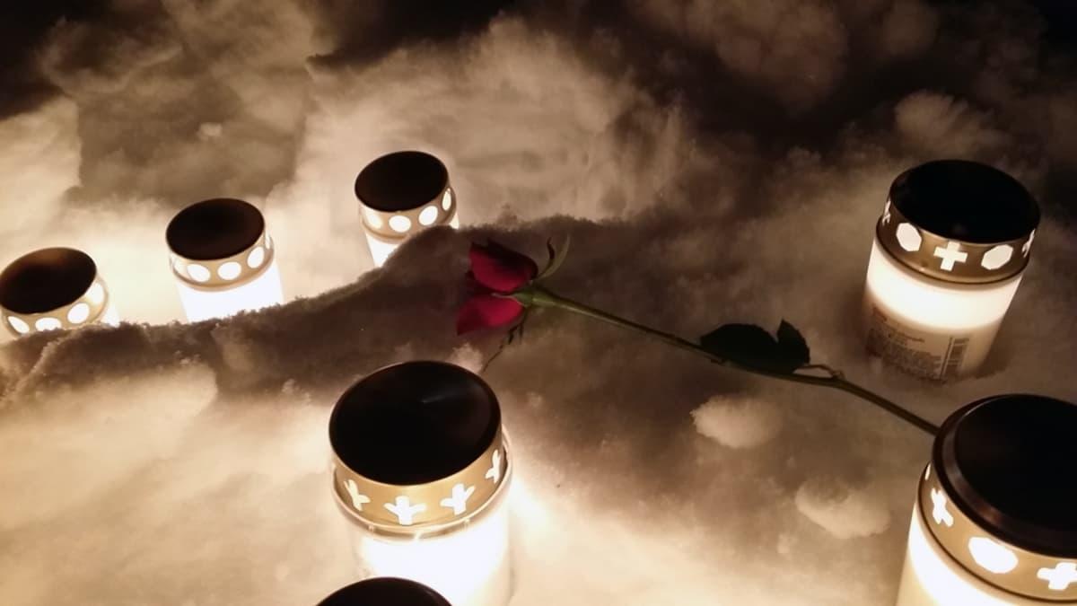 Hautakynttilöitä ja punainen ruusu lumihangessa