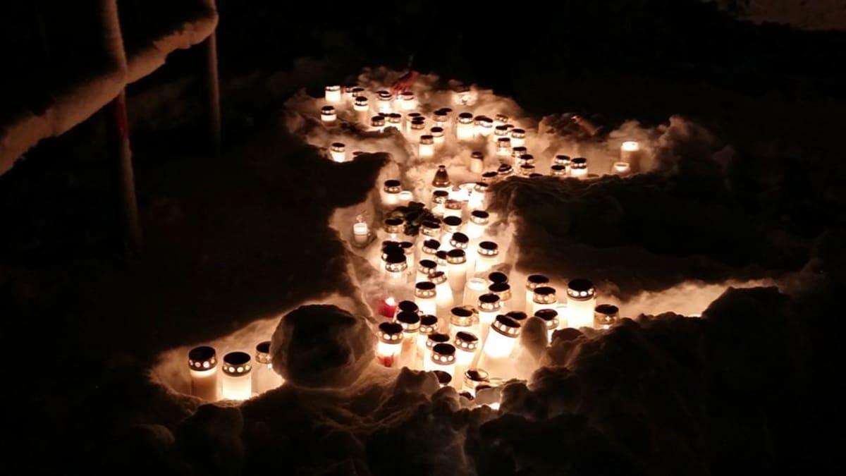 Hautakynttilät lumihangessa pimeän keskellä