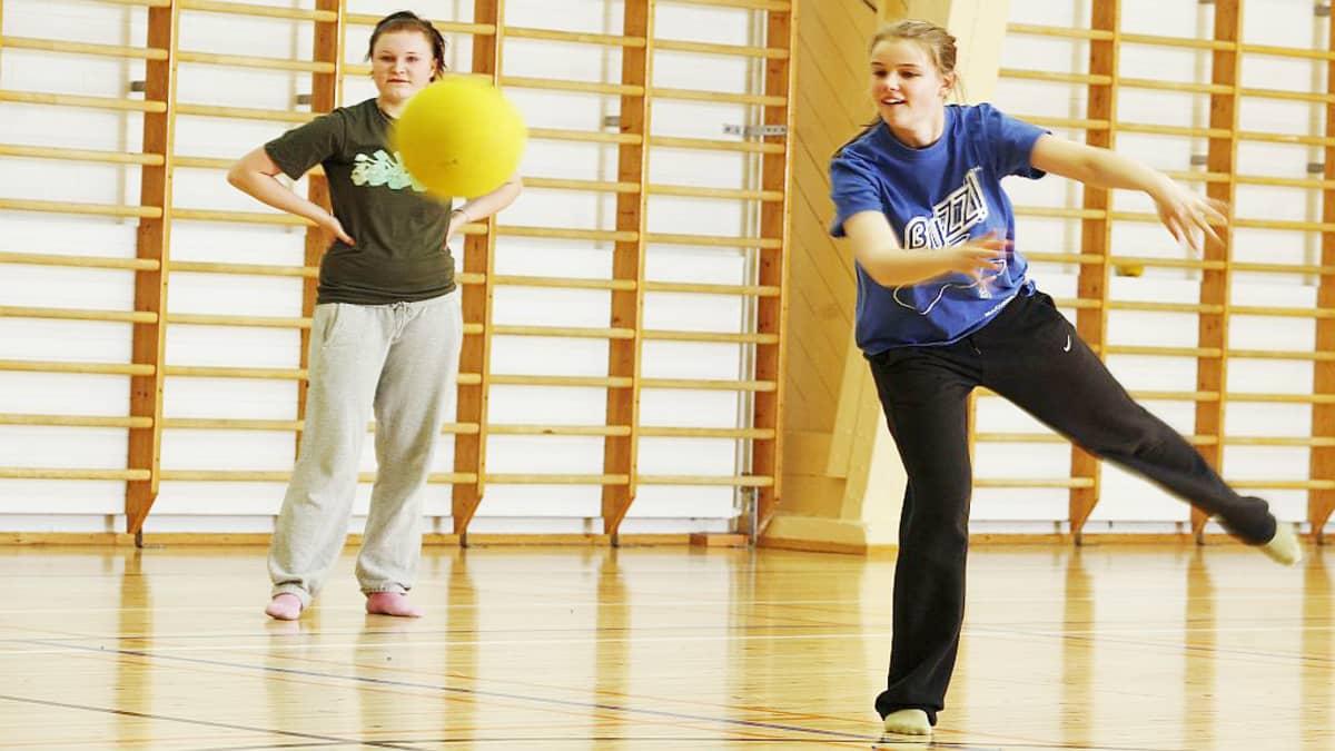 Kaksi tyttöä pelaa palloa liikuntasalissa.