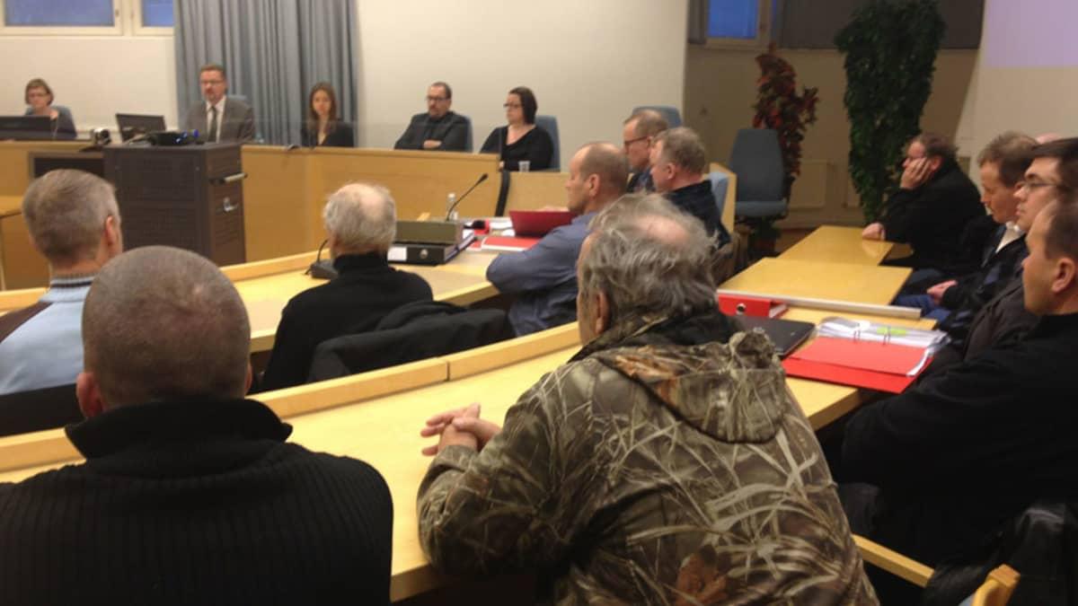 Kuva käräjäsalista, istuvia ihmisiä, taustalla istuva oikeus.