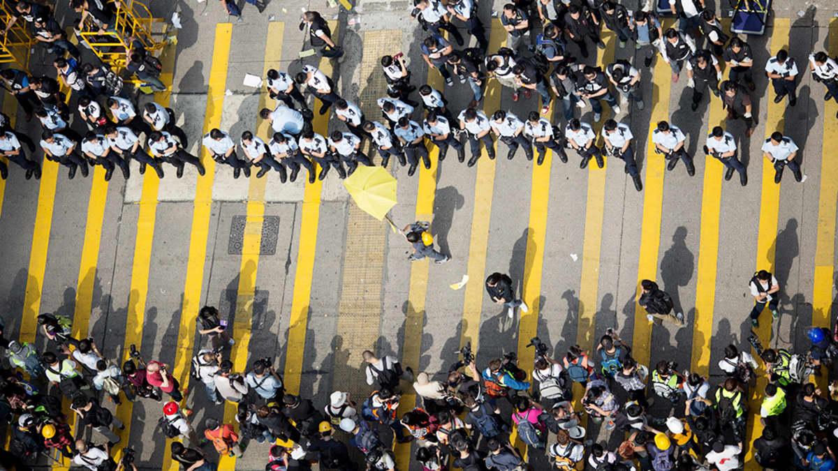 Mielenosoittajia ja poliiseja kadulla Hongkongissa.