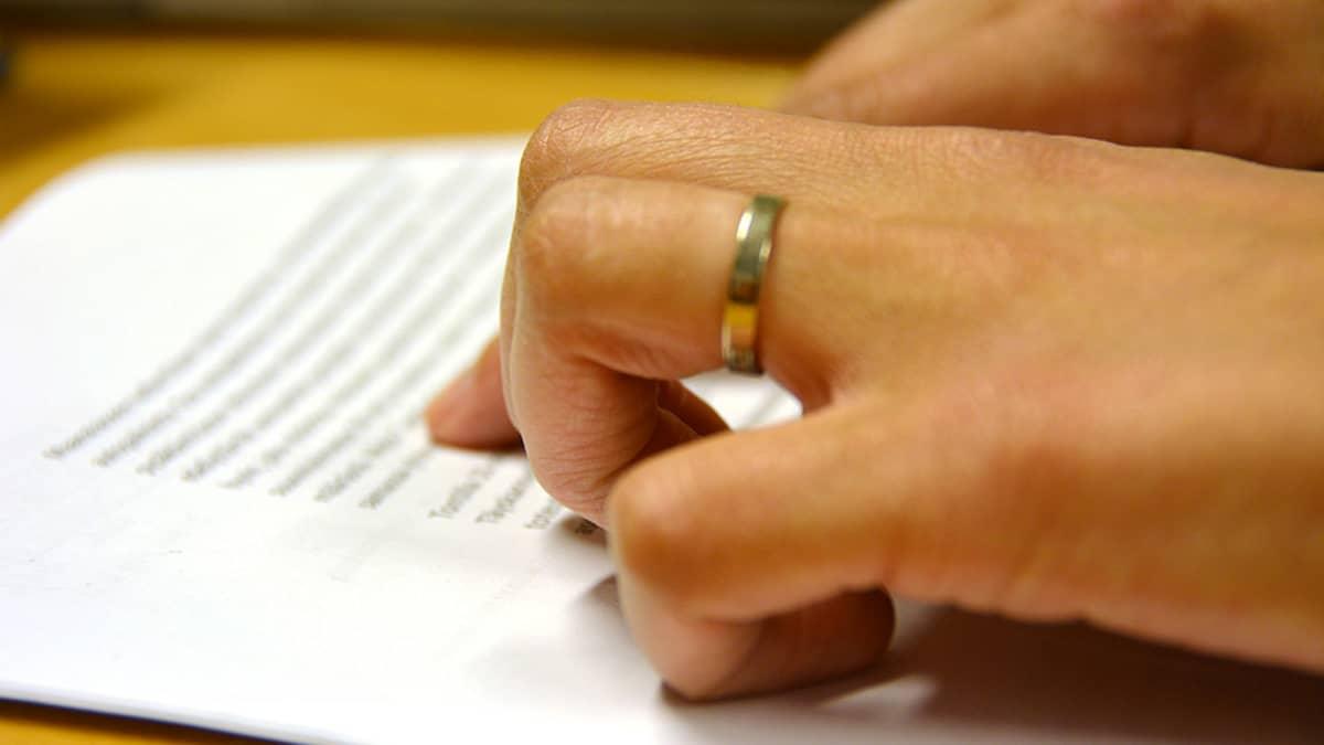 Kuvassa nainen kuljettaa sormia tekstin päällä