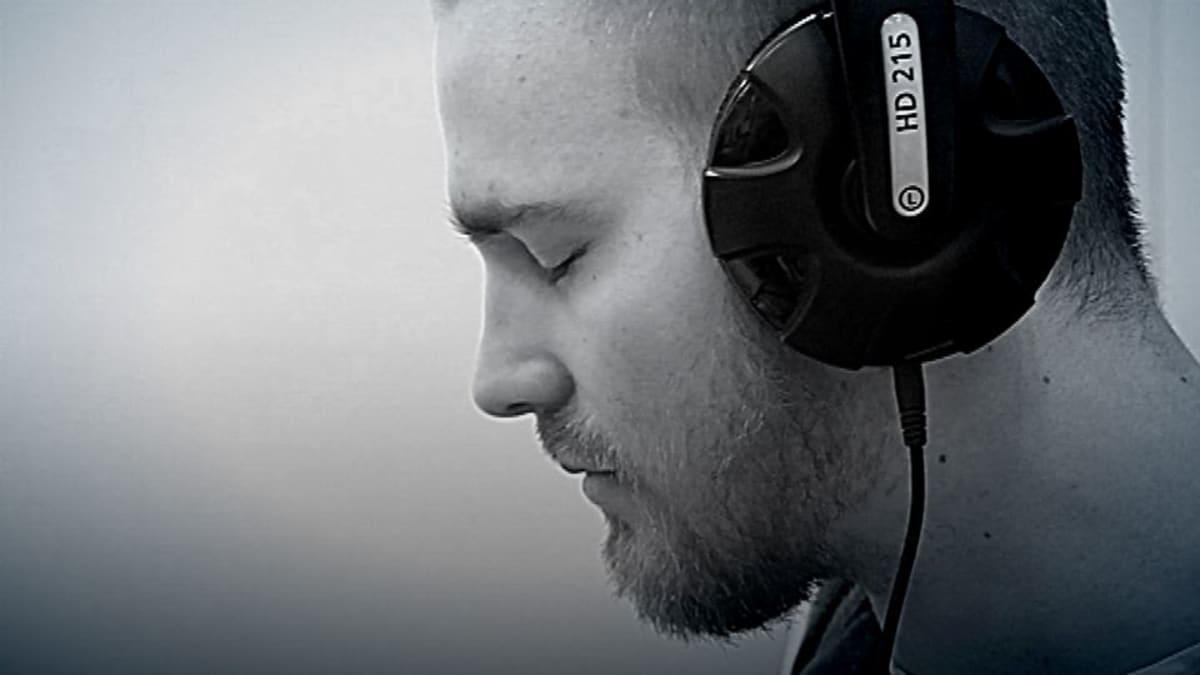 Mies kuuntelee kuulokkeilla musiikkia.