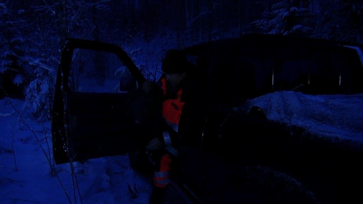 Mies nousemassa autosta pimeässä.