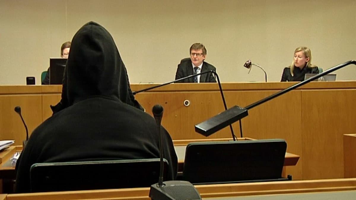 Huppariin pukeutunut syytetty käräjäoikeuden kuultavana.
