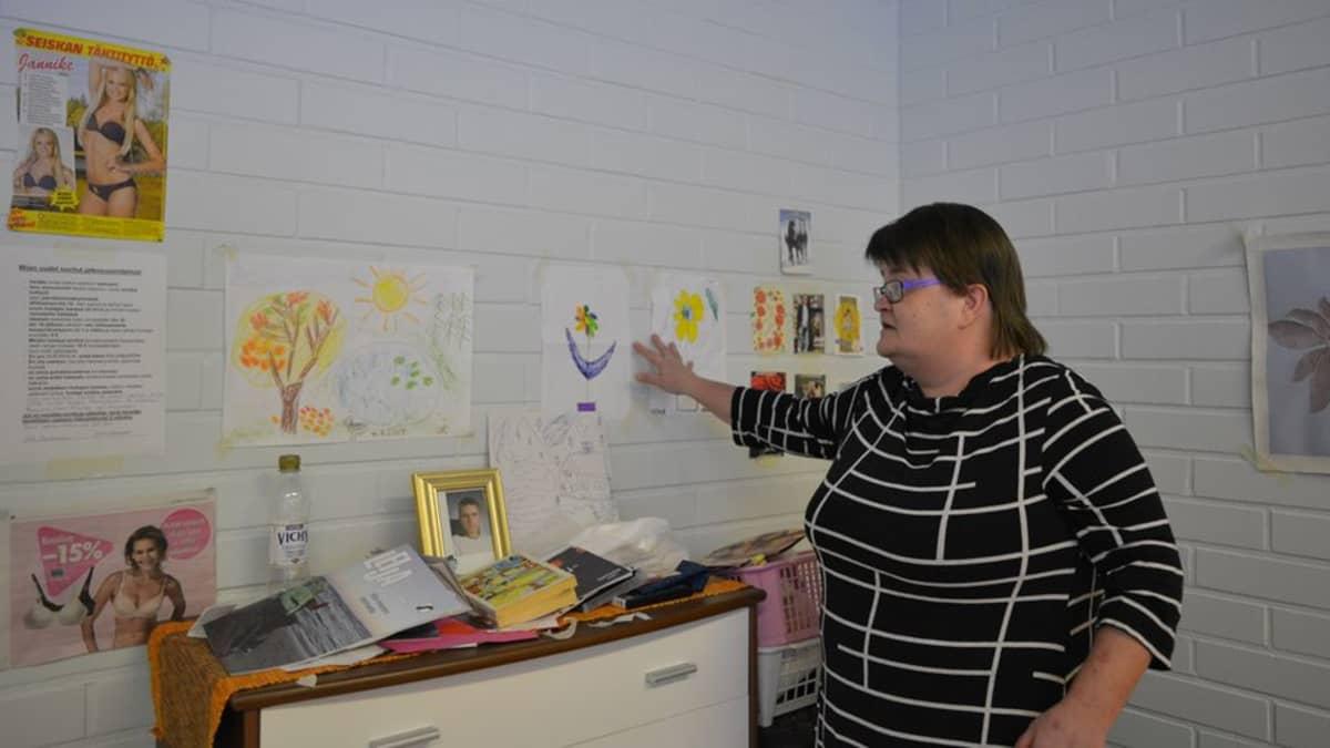 Mia Korhonen esittelee ystäviltään saamia piirrustuksia palvelukeskuksessa sijaitsevassa omassa huoneessaan.