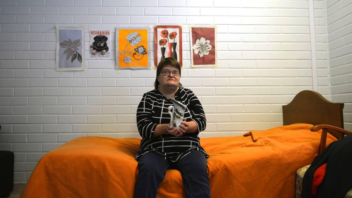 Mia Korhonen istuu palvelukeskuksessa, oman huoneensa sängyllä ja pitää sylissä rakkaita korsite-esinettä, joutsenmaljakkoa.