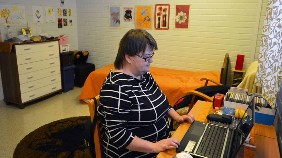 Mia Korhonen istuu palvelukeskuksessa omassa huoneessaan, pöydän ääressä tietokoneella.