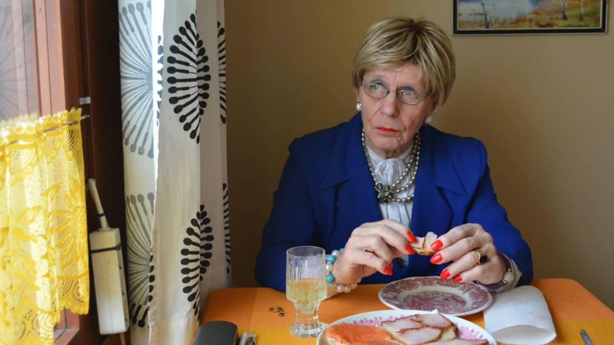 Mieheksi pukeutunut nainen istuu keittiönpöydän ääressä ja syö voileipää.