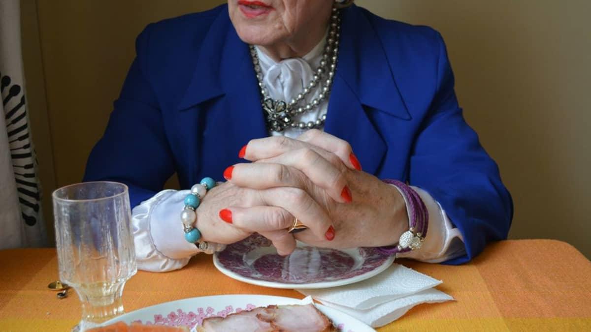 Mieheksi pukeutunut nainen istuu pöydän ääressä, lähikuvassa kädet.