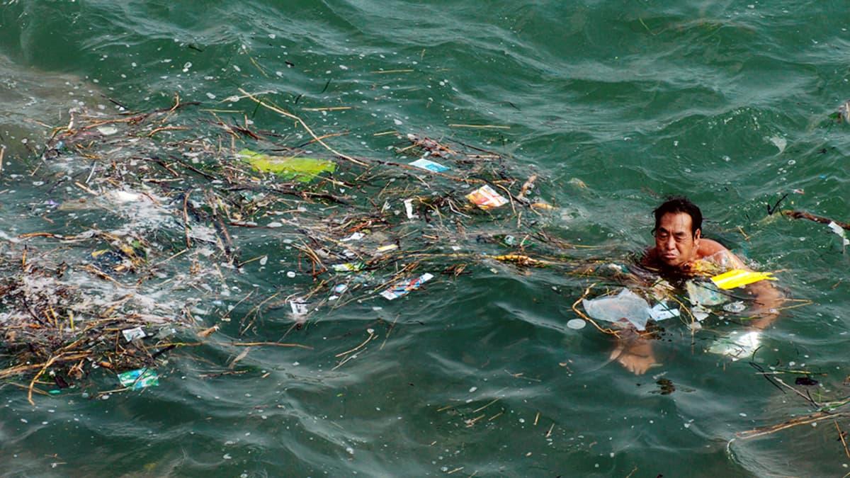Kiinalainen mies ui meressä kelluvien roskien keskellä Qingdaossa.