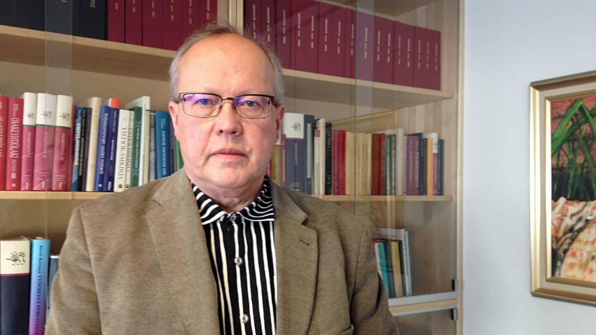 Antti Kejo poseeraa hyllyn edessä.